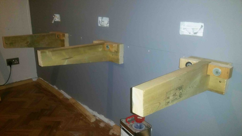 picture showing three timber support brackets attached to a wall securely fixed to the wall using screws