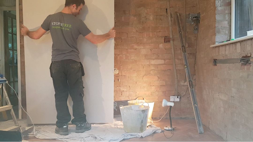 sam fixing his first ever plasterboard to a wall