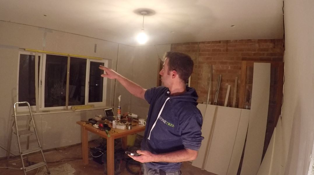 sam pointing towards window he'd just covered in plasterboard