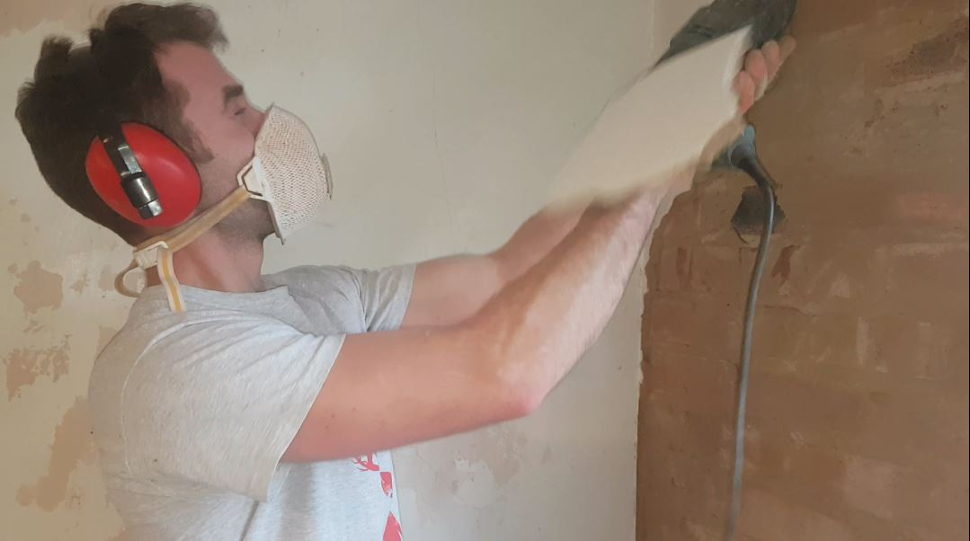 a picture of same chiseling out some plaster and getting hit by falling boards