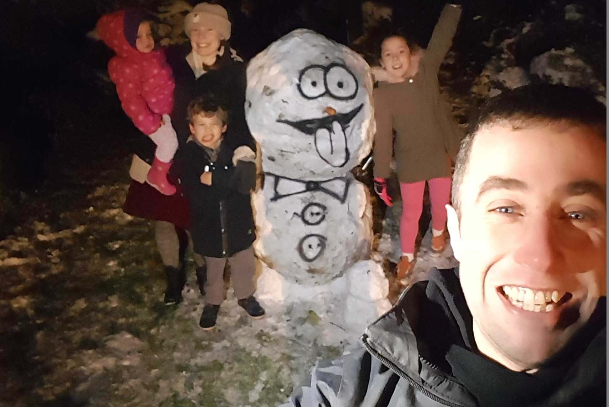 funny picture showing sam with his family after making a real snowman