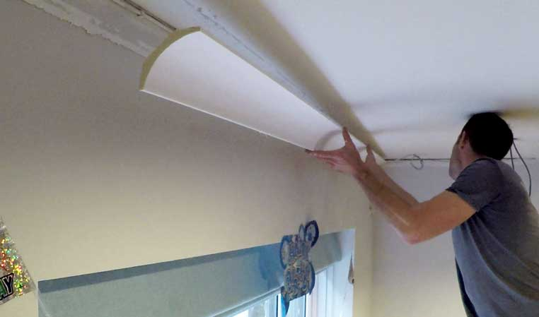 sam reaching up, placing coving onto wall and ceiling corner