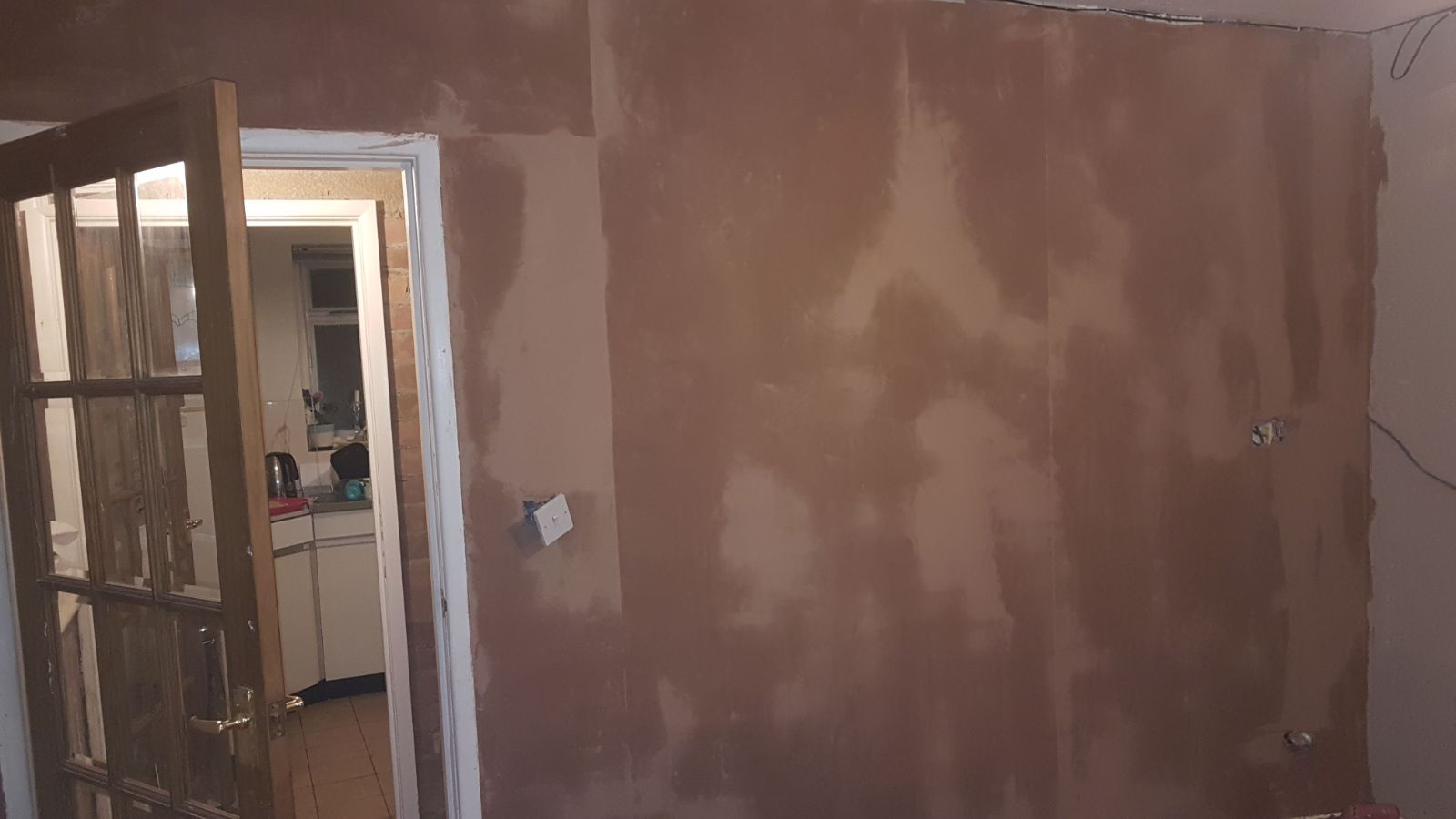 picture of a newly plastered wall, still a bit damp but drying out nicely