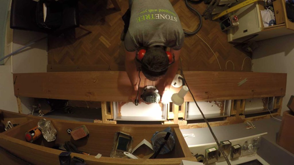 birds eye shot of sam routering out recesses in the worktop timber for his desk