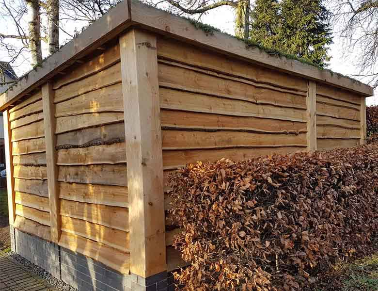 Picture showing rustic shed with green roof, sides clad in larch waney edge with chunky corner posts