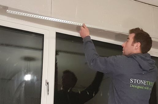 sam holding a metal bead up to the corner of a window recess, about to stick it onto the plasterboard using scrim tape