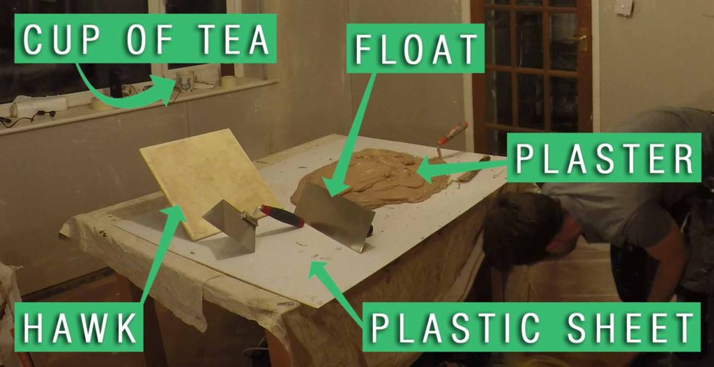 picture showing a table with a plastic sheet over the top. tools and plaster are on the sheet