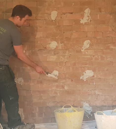 picture of sam using a garden trowel to slop adhesive onto a wall