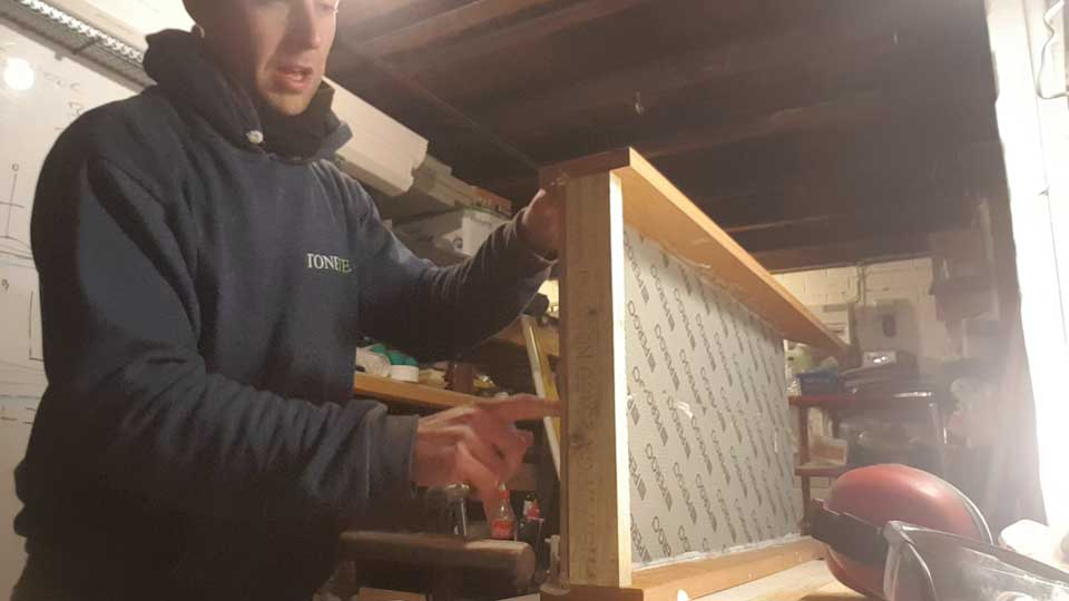 screwing the back board onto the sledge body using a drill
