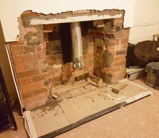 plaster all knocked off fireplace showing bricks. hearth installed but covered in cardboard. flu dangling down into fireplace