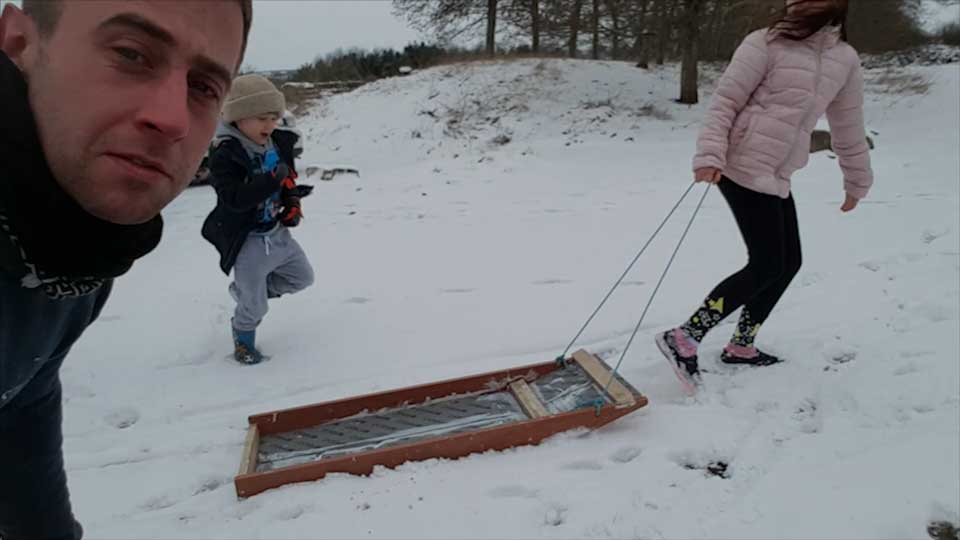 Ari dragging the sledge through the snow. Showing the front end tilted upwards so that the sledge stays above the snow