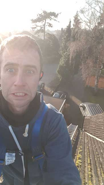 I have a worried look on my face as I'm standing on the roof. Picture is angled down the roof pitch to show how high it is