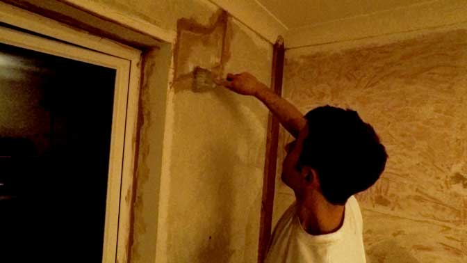 sam using a scraper to squeeze bonding coat into th gaps around the plasterboard