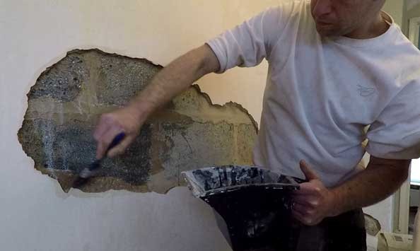 sam using a paint brush to apply pva to the masonry and edges of the plaster