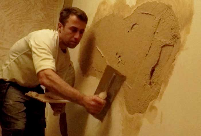 sam scraping the trowel along the edges of the existing plaster