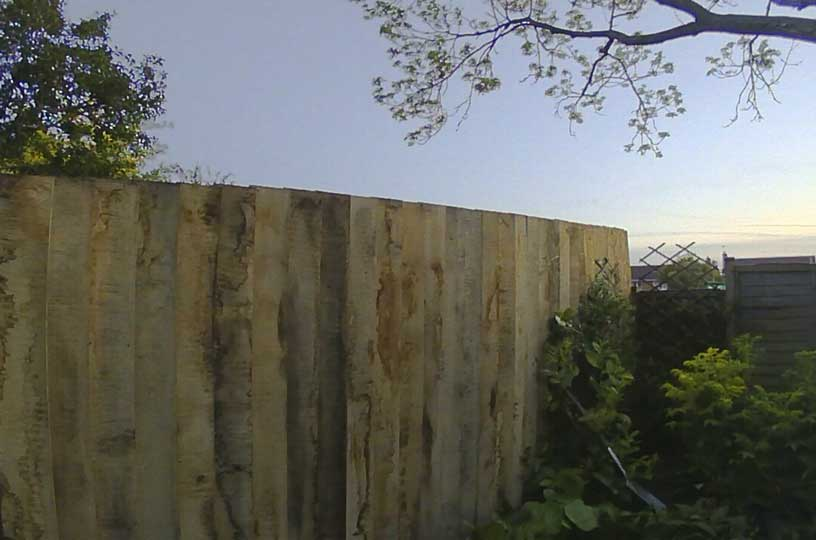 finished oak feather boarded fence with sunset in background