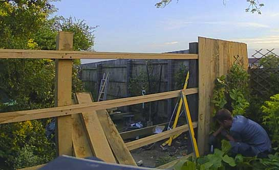 half constructed fence showing post and cant rails with about a quarter of the feather boards attached