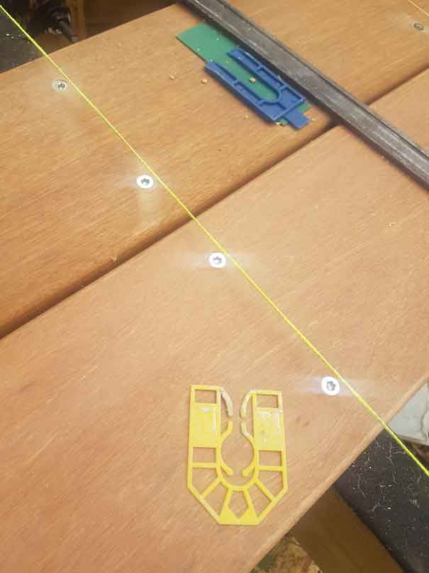 a couple of decking boards with a stringline going over the top, which is lined up with the  joist below. There are four screw heads showing (two per board) that are in-line with the screw heads