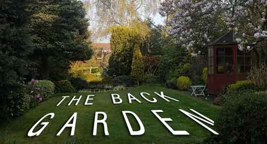 "photo of rear garden the with text written on the lawn reading ""the back garden"""