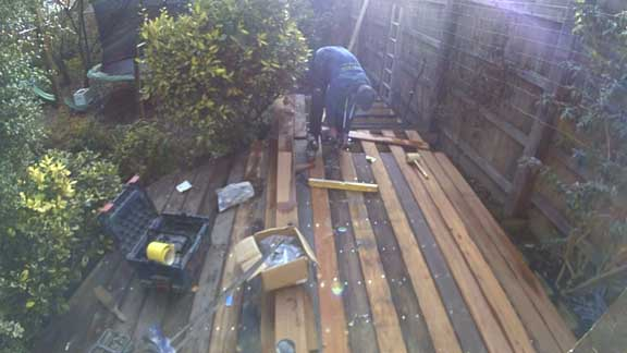sam working on his decking. most of the boards are down and sam is using a drill to attach the remaining ones