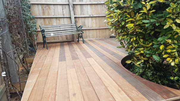 decking planks laid away from the camera with a bench in the background and sams new fence