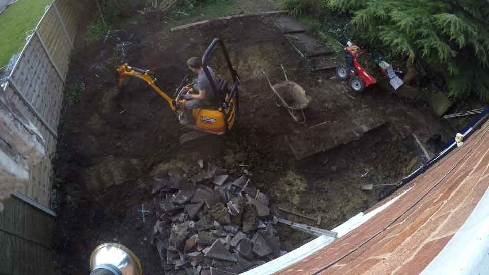 view from 1st floor looking down onto the digger, with sam on it digging the foundations and stripping the site
