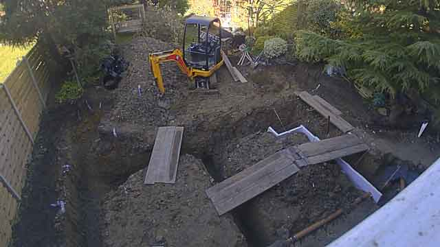 top down picture showing excavated foundations ready for concrete pouring. Planks have been laid over the trenches to allow wheelbarrow access with the concrete. claymaster heave protection has been fixed to the sides of some trenches.